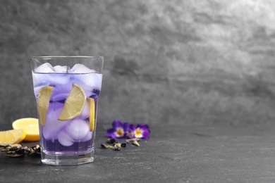 Organic blue Anchan with lemon in glass on grey table, space for text. Herbal tea