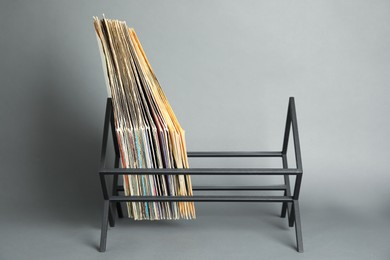 Rack with vinyl records in sleeves on grey background