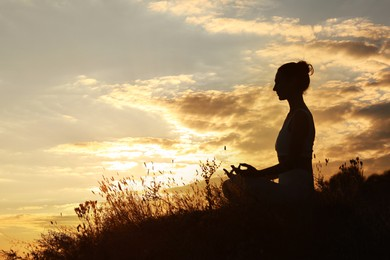 Silhouette of woman meditating outdoors at sunset. Space for text