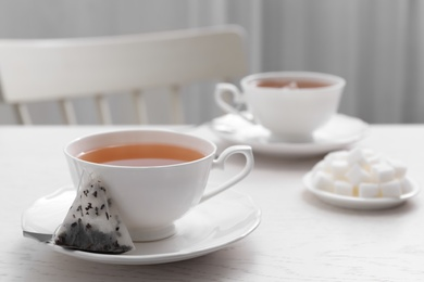 Tea bag and cup of hot drink on white wooden table. Space for text