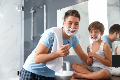 Dad and son with shaving foam on their faces in bathroom