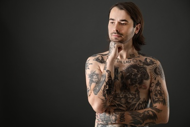 Young man with tattoos on body against black background. Space for text