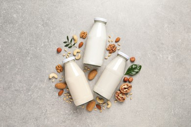 Vegan milk and different nuts on grey table, flat lay