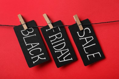 Tags with words Black Friday Sale on rope against red background