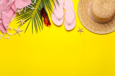 Flat lay composition with different beach objects on yellow background, space for text