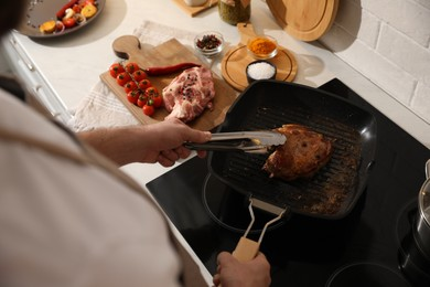 Man taking cooked meat from frying pan, above view