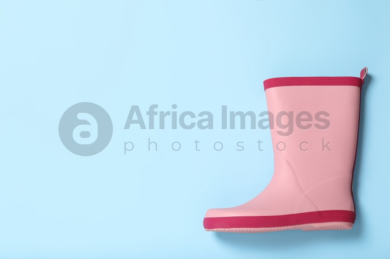 Pink rubber boot on light blue background, top view. Space for text