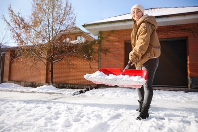 Young woman shoveling snow outdoors on winter day