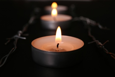 Burning candle and barbed wire on black background, closeup. Holocaust memory day