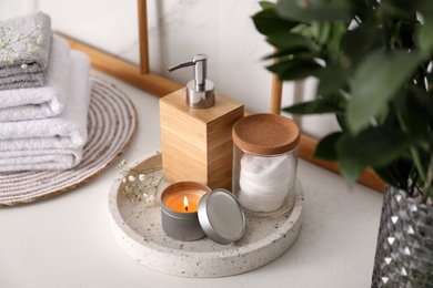 Tray with soap dispenser, cotton pads and burning candle on countertop in bathroom