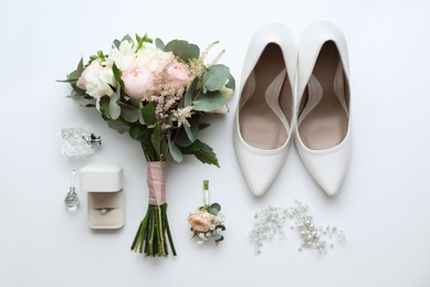 Composition with wedding high heel shoes on white background, top view