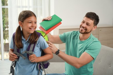 Father helping his daughter to get ready for school at home