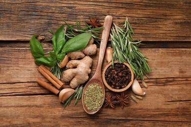 Flat lay composition with different natural spices and herbs on wooden table
