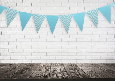 Empty wooden table and decorative bunting flags hanging on brick wall