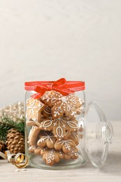 Tasty Christmas cookies in glass jar and festive decor on beige wooden table