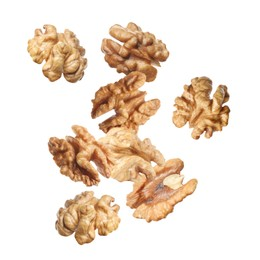 Halves of walnuts falling on white background