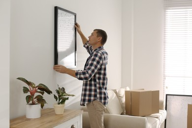 Man hanging picture on white wall in room. Interior design