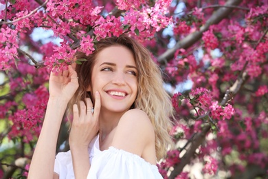Attractive young woman posing near blossoming tree on sunny spring day