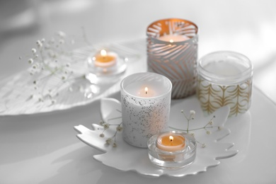 Burning candles in beautiful holders and flowers on table indoors
