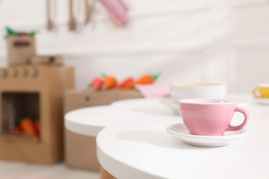 Cup on white table in kitchen, space for text