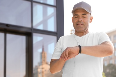 Handsome mature man looking at fitness tracker on street. Healthy lifestyle