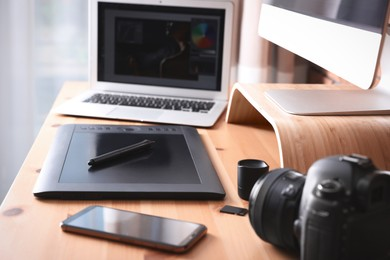Modern retoucher's workplace with different digital devices on wooden table