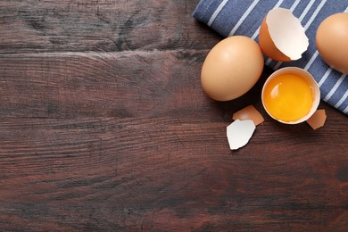 Whole and cracked chicken eggs on wooden table, flat lay. Space for text