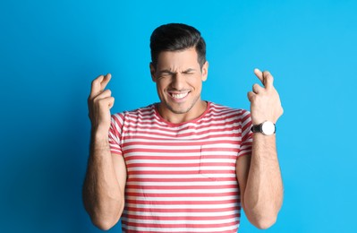 Man with crossed fingers on light blue background. Superstition concept