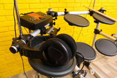 Modern electronic drum kit with headphones indoors. Musical instrument