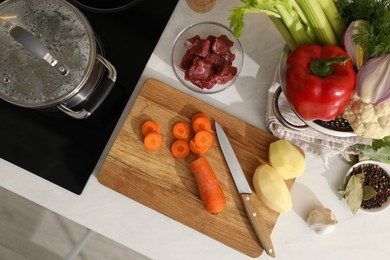 Homemade bouillon recipe. Fresh ingredients on countertop near cooktop, flat lay