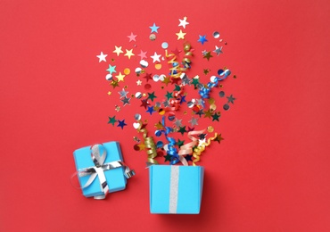 Box with bright confetti on red background, flat lay