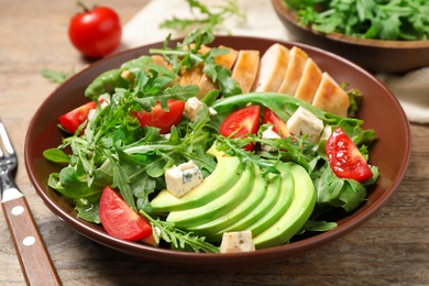 Delicious salad with chicken, arugula and avocado on wooden table, closeup