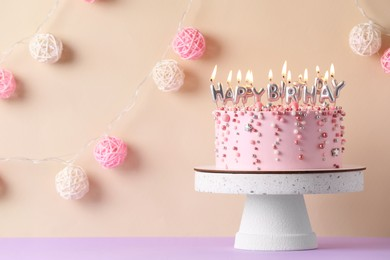 Birthday cake with burning candles on violet table, space for text