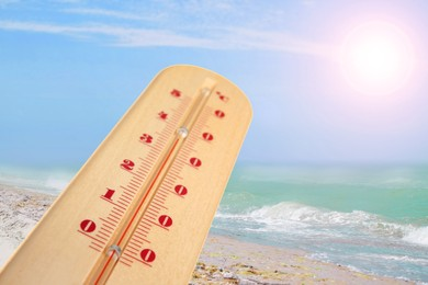 Closeup view of weather thermometer and beautiful seashore on background. Heat stroke warning