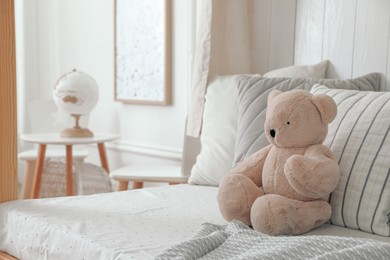 Comfortable bed with cushions and toy in room. Interior design