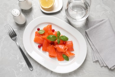 Salmon carpaccio with cranberries and basil served on grey table, flat lay