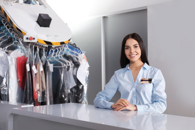 Female worker near counter at modern dry-cleaner's