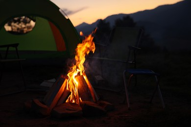 Beautiful bonfire and folding chairs near camping tent outdoors in evening