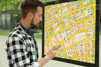 Young man with smartphone near public transport map at bus stop