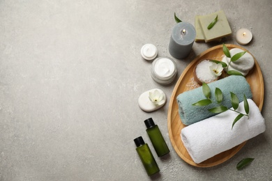 Flat lay spa composition with skin care products on grey textured table, space for text