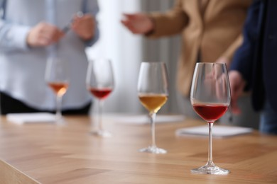 Sommeliers making notes during wine tasting at table indoors, closeup