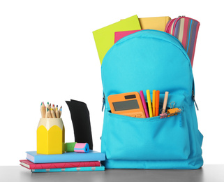 Bright backpack with school stationery on grey stone table against white background