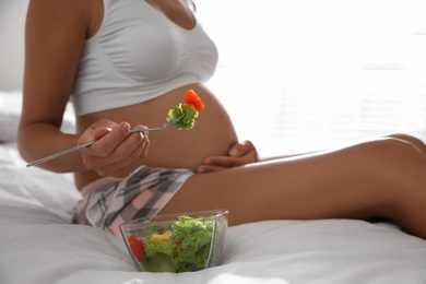 Young pregnant woman with bowl of vegetable salad in bedroom, closeup. Taking care of baby health
