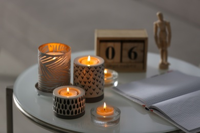 Burning candles in holders and notebook on white table indoors