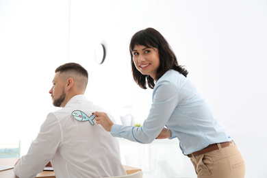 Young woman sticking paper fish to colleague's back in office. April fool's day