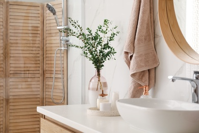 Vase with beautiful branches, candles and toiletries near vessel sink in bathroom. Interior design