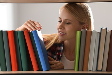 Woman searching for book on shelf in library
