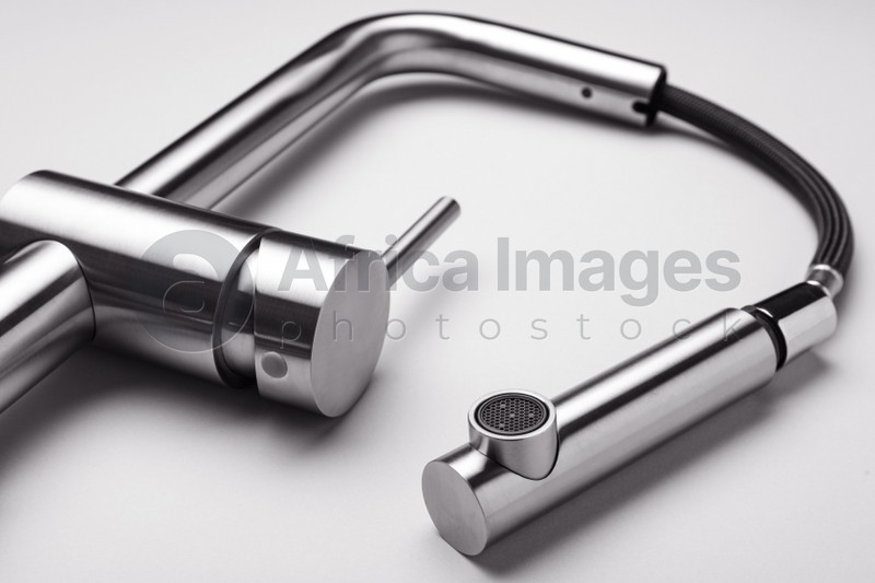 Modern pull out kitchen faucet on grey background, closeup