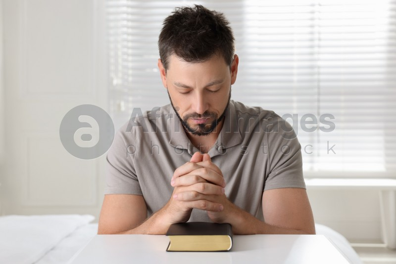 Religious man with Bible praying at home