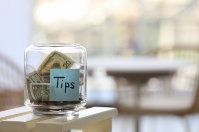 Glass jar with tips on table indoors. Space for text